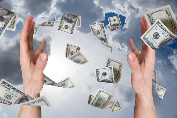 Money falling from the sky, two outstretched hands trying to catch it.