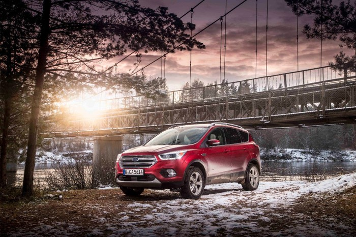 Ford's Kuga parked in front of a bridge against a snow-dusted landscape.