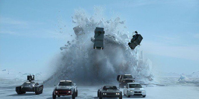 A fleet of vehicles racing on a snow surface, with an explosion in the background sending cars and snow flying in the air.