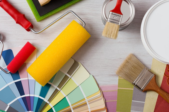An assortment of paint, rollers, color samples, and brushes.