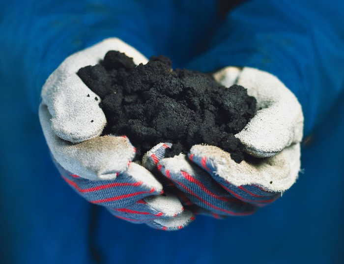 Bitumen held by white gloves.