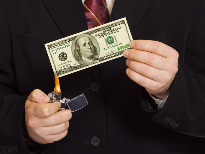 Man in suit burning $100 bill with a lighter