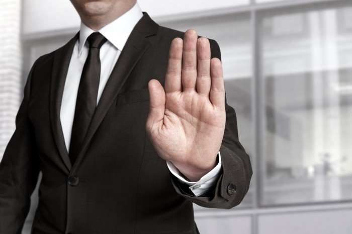 A businessman holds up his hand in a stop gesture.