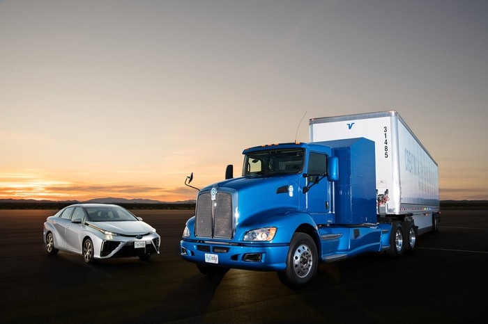 A white Toyota Mirai sedan next to the electric truck.