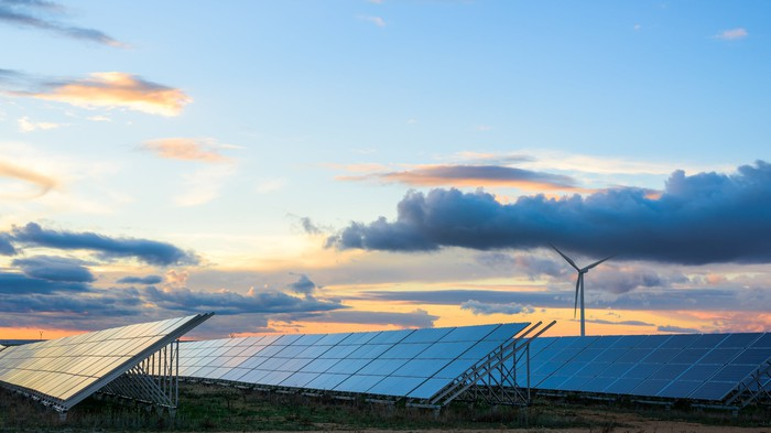 A solar farm with a wind turbine in the background shown at dusk.