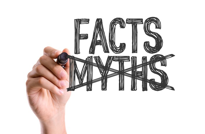 Hand with marker writing the word Facts and crossing out Myths