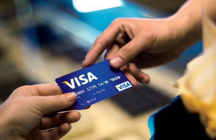 One hand handing a Visa credit card to another.