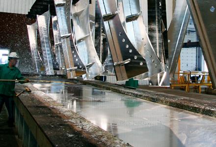 Worker galvanizing a piece of steel