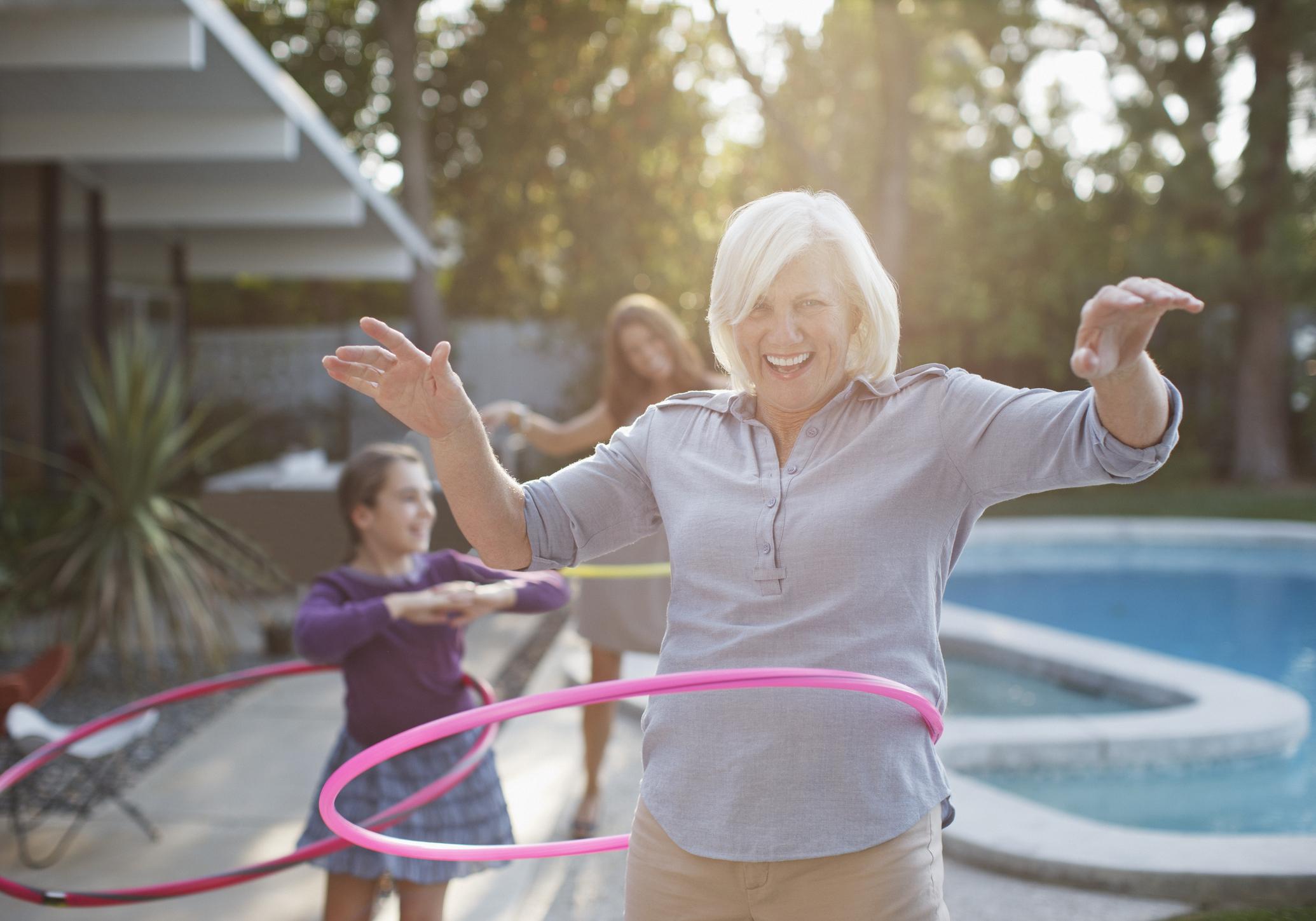 A happy senior woman by a pool uses a hula hoop.