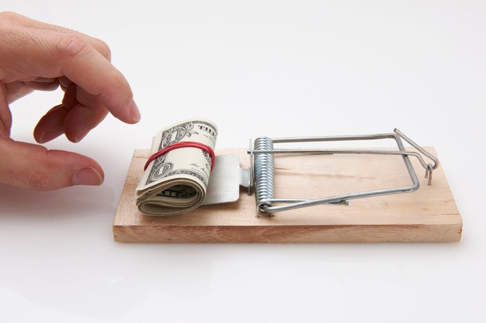A hand reaching for money in a mouse trap.