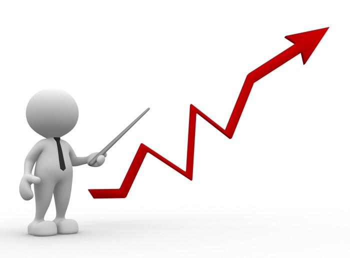 Faceless figure in a tie holding a pointer next to a red stock chart going up.
