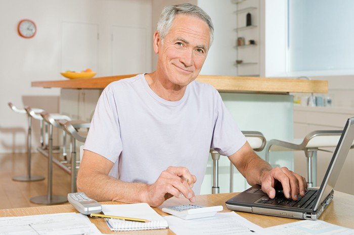 A senior man calculating his Social Security benefit and examining his finances.