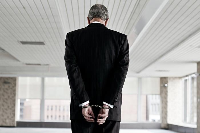 Executive in handcuffs.