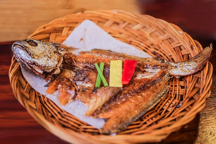 A cooked fish in a basket.