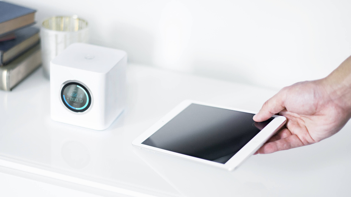 Amplifi router with hand laying down a tablet