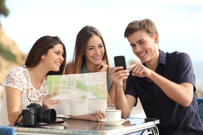 Three friends staring at a map and reviewing on their mobile phone.