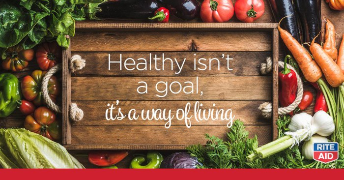 "Rite Aid ad with healthy foods surrounding a wooden tray that reads ""Healthy isn't a goal, it's a way of living."""