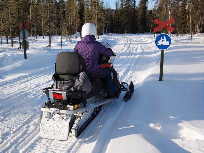 Snowmobiler facing no snowmobiles sign.