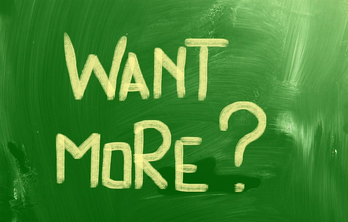 """Want more?"" painted in yellow on green background"