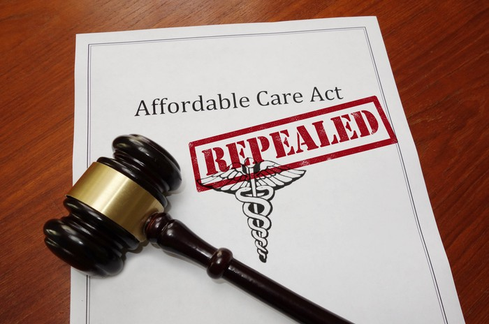 """A judge's gavel sitting atop an Affordable Care Act plan with the word """"repealed"""" stamped on the plan."""