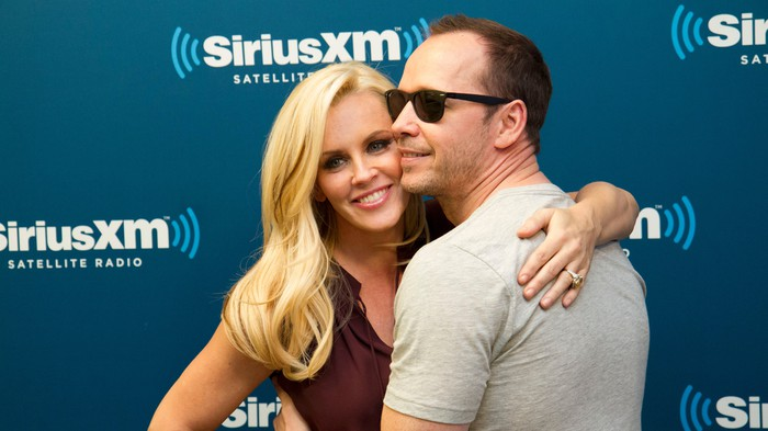 Jenny McCarthy with Donnie Wahlberg in front of a Sirius XM sign.
