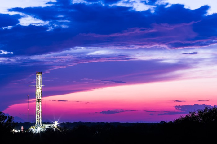 A drilling rig with a pink and blue sky background