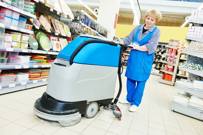 A woman operates a commercial floor scrubber at a retail store.