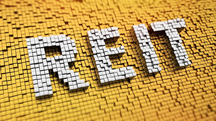 Pixelated acronym REIT made from cubes, mosaic pattern.