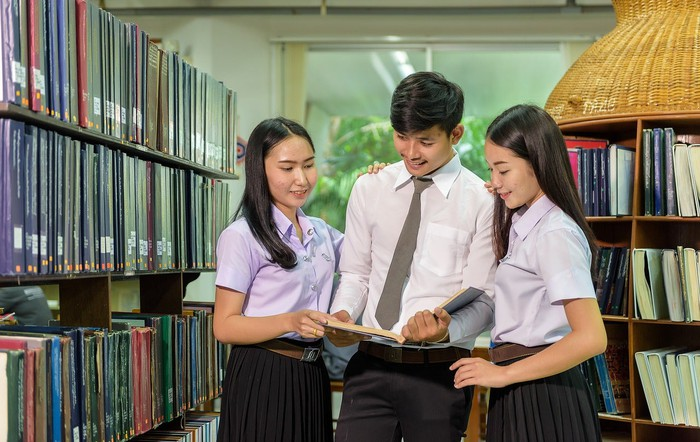 Three students looking at a book.