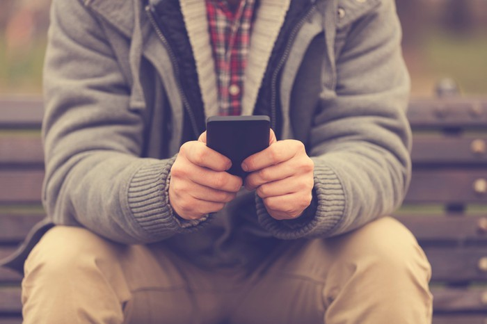 A person sitting uses his smart phone to text someone.