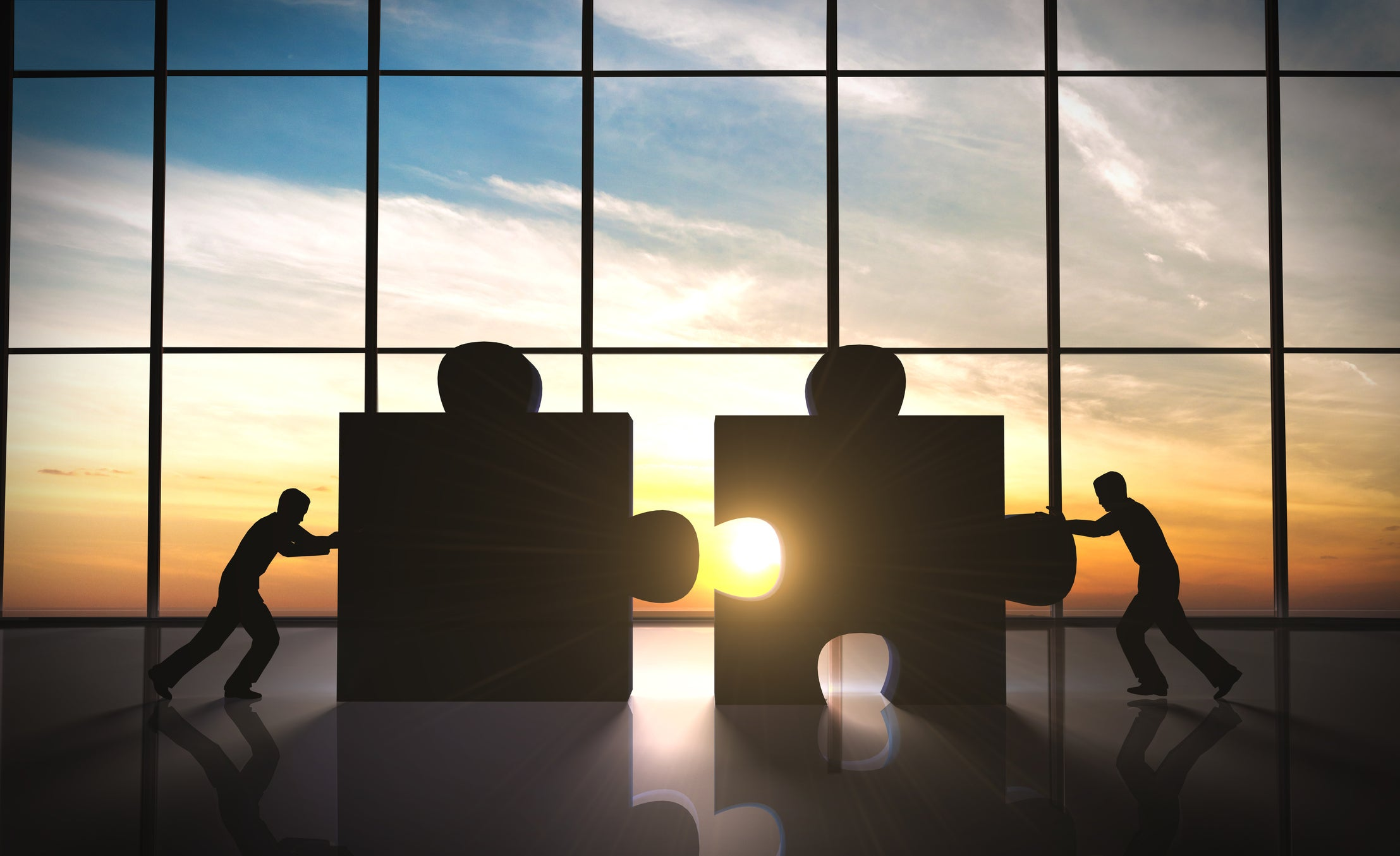 Business people push together two over-sized puzzle pieces in a board room.