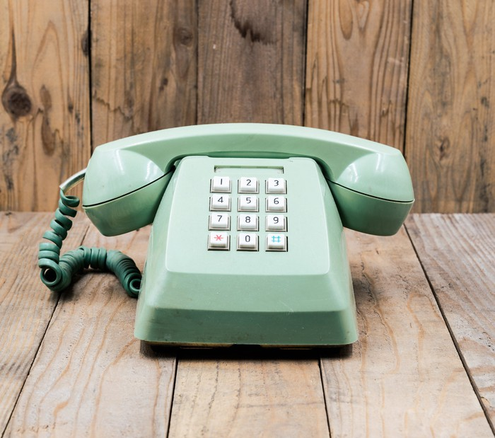 An old-fashioned green telephone rests on a table.