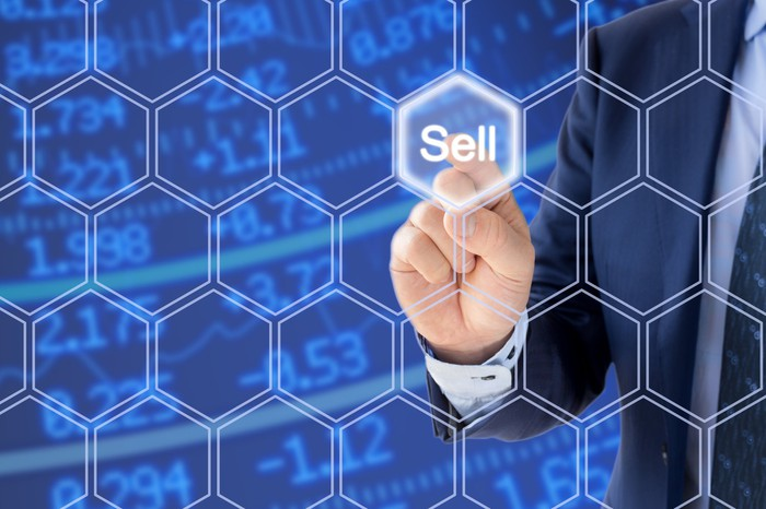 Man pushing sell button