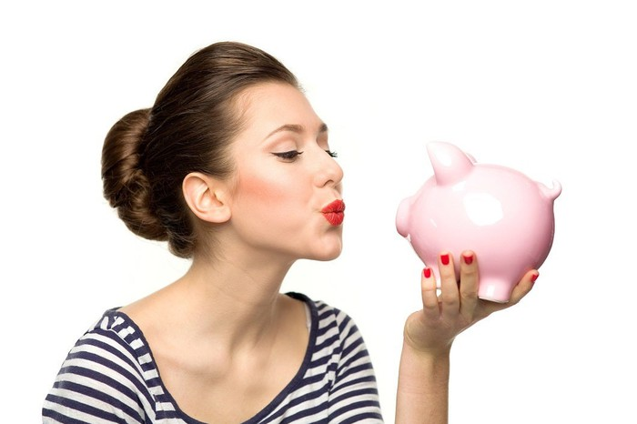 Woman blowing a kiss to a piggy bank