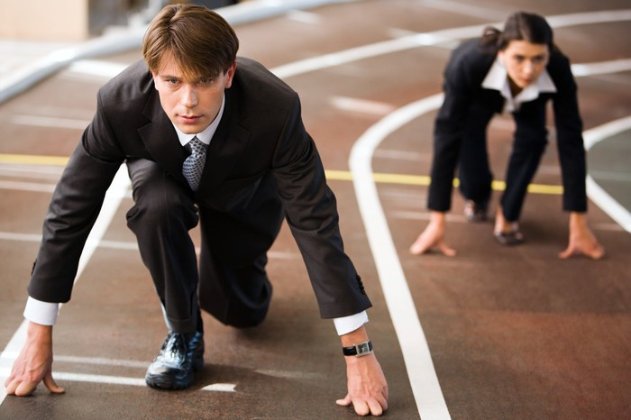 Two businesspeople at the starting line of a track competition.