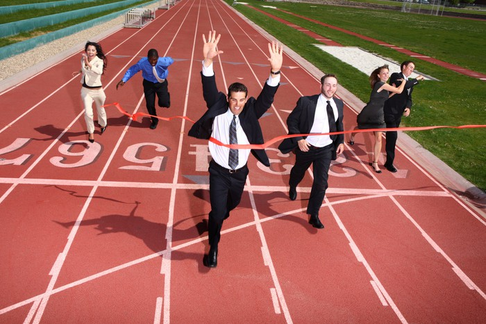 Business people running a race on a track reach the finish line.