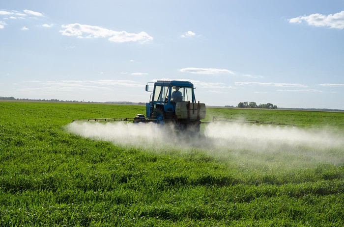 Tractor spraying pesticide chemicals on a field of crops