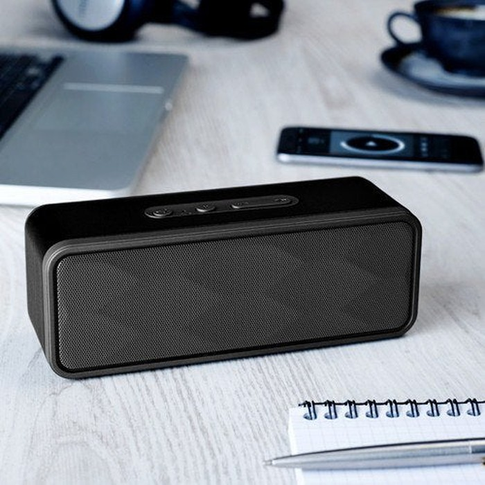 A speaker on a tabletop, with other items including a laptop, a cup of coffee, a pen, and paper.