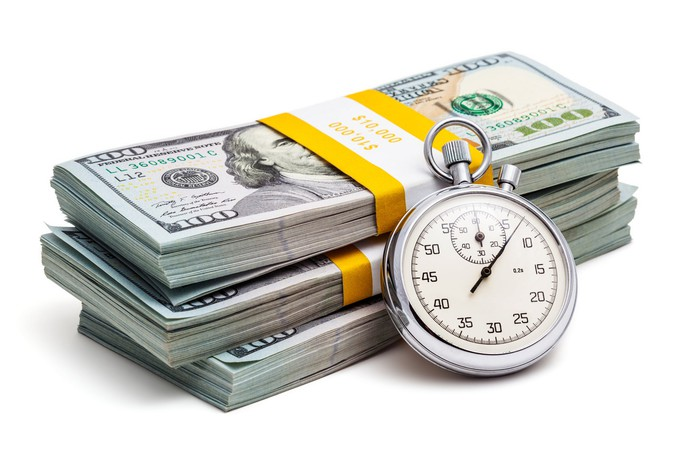A stopwatch leaning against a pile of cash.