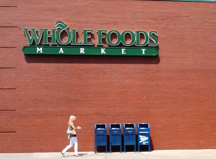 A sign on an outside  wall of a Whole Foods