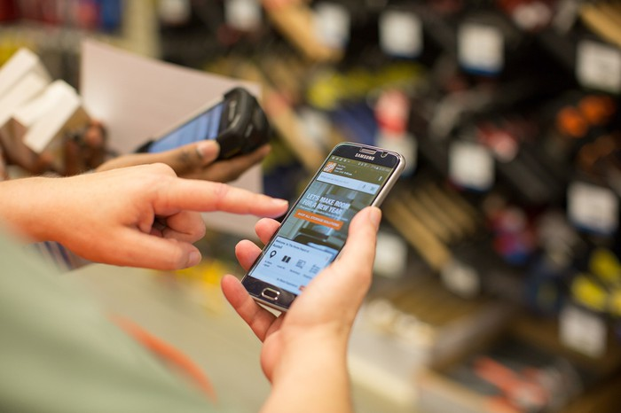 Hands holding mobile phone using The Home Depot app.