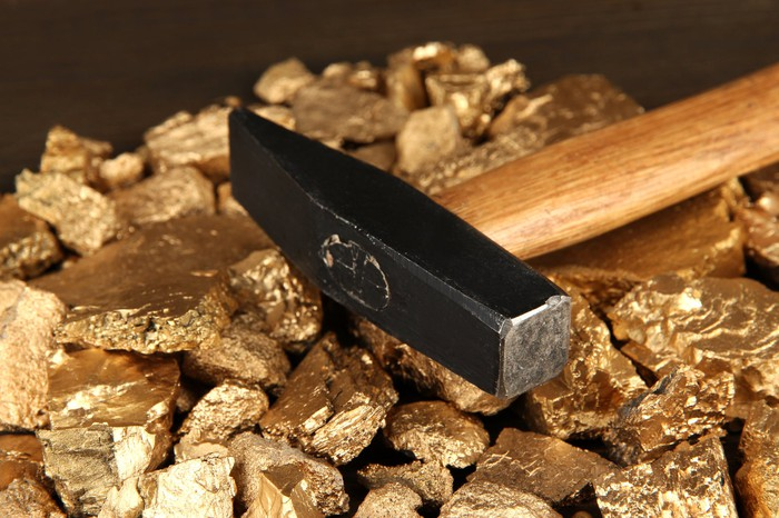 Golden nuggets with hammer on wooden background.