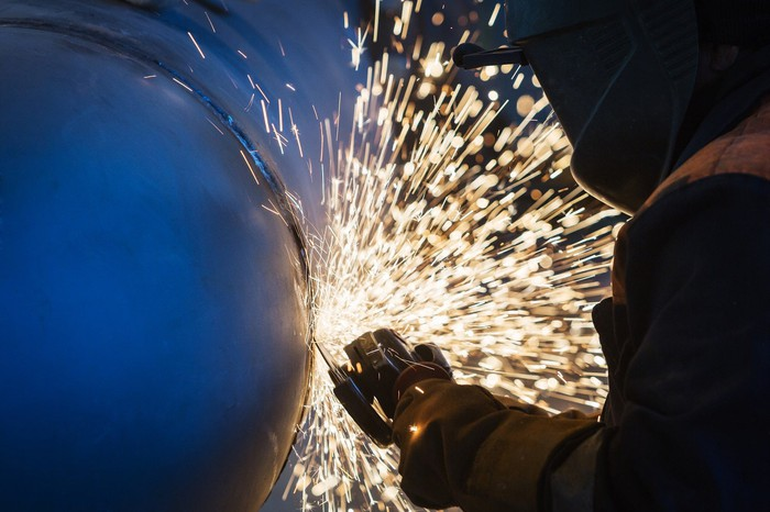 A worker uses a grinder on a welded steel tube.