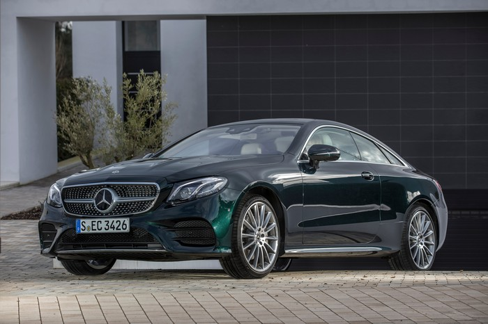 A green Mercedes-Benz E-Class coupe.