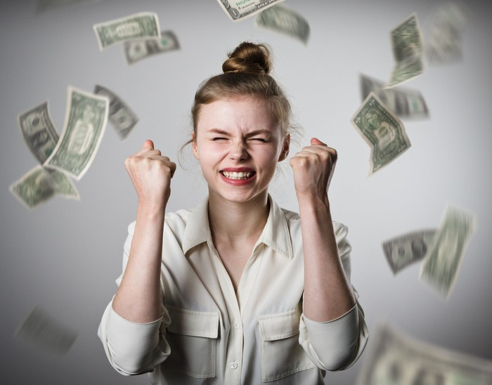 woman celebrating as dollar bills rain down all around her