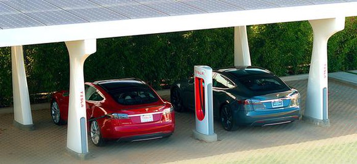 Tesla cars charging at a Supercharger site