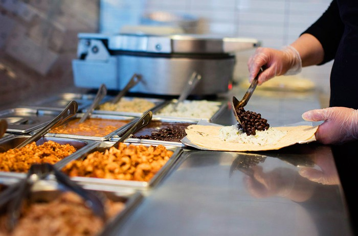 worker puts black beans on a tortilla