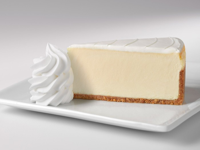 The original recipe-style cheesecake, served with a side of whipped cream on a white plate.
