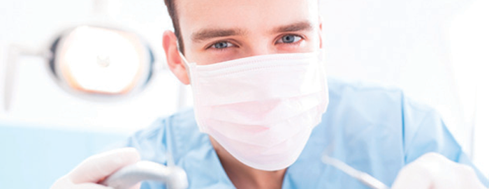 A dentist with a mask, holding dental implements, and looking at the camera.