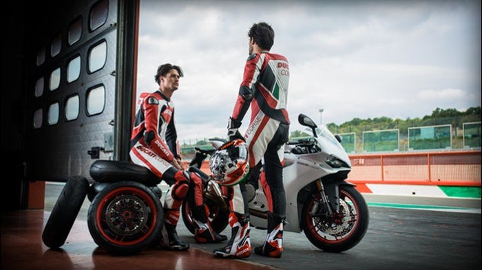 Two motorcyclists by a Ducati motorcycle